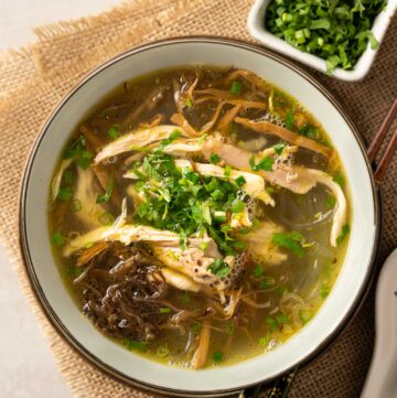 a bowl of chicken glass noodle soup with bamboo shoots