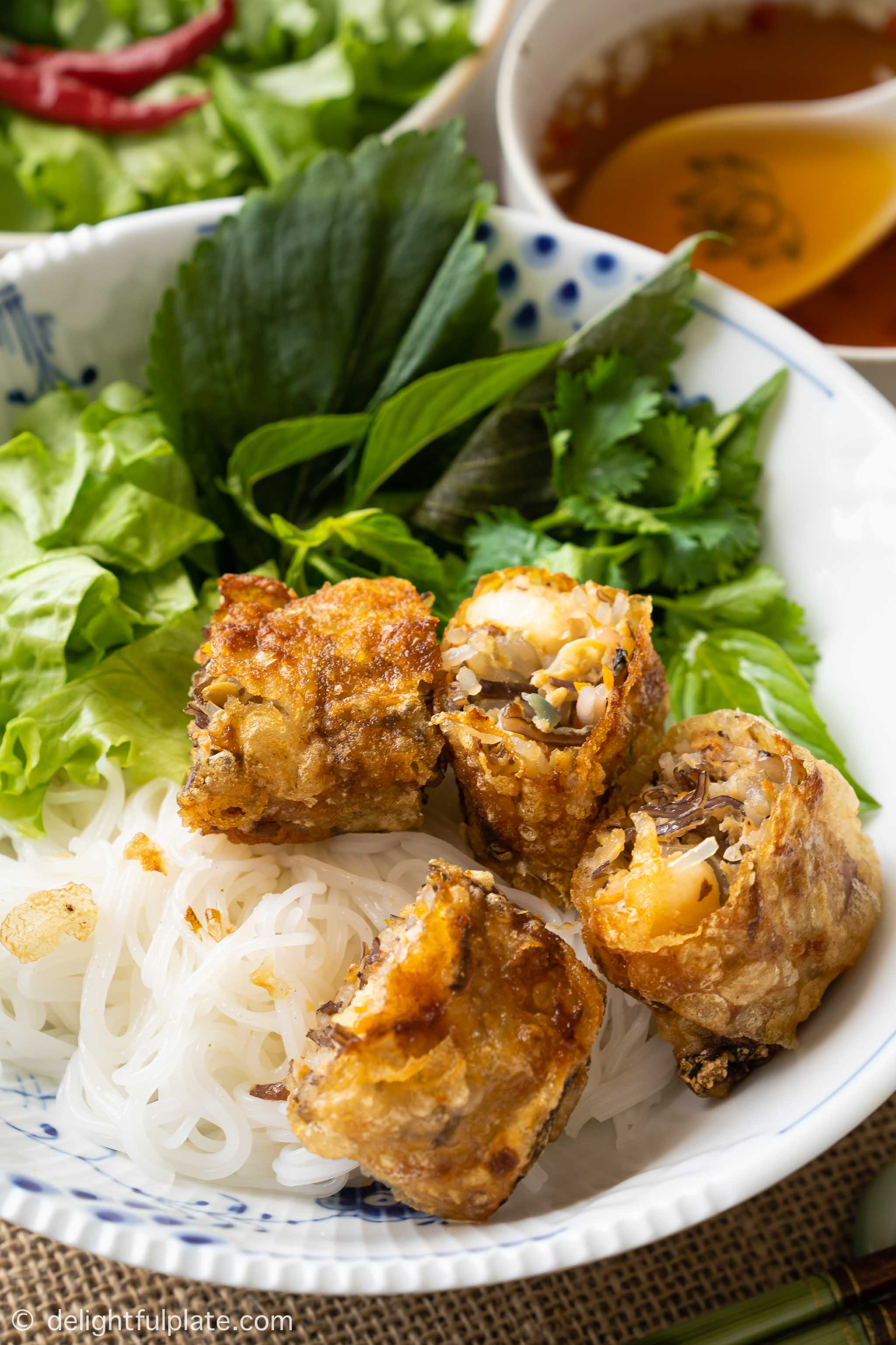 a bowl of rice vermicelli noodles, fried spring rolls, lettuce and fresh herbs