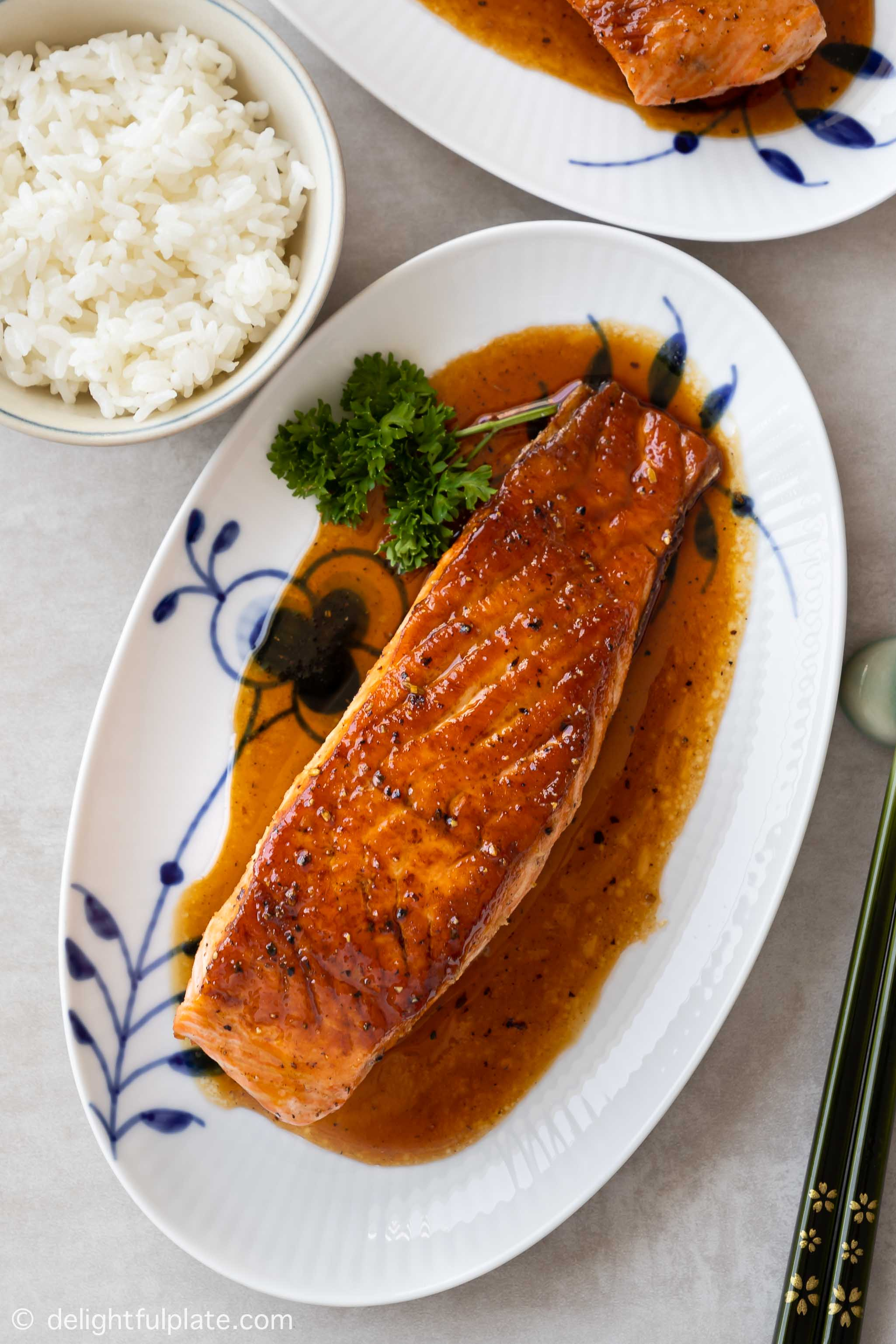 a glazed salmon fillet on a serving plate, accompanied with steamed rice