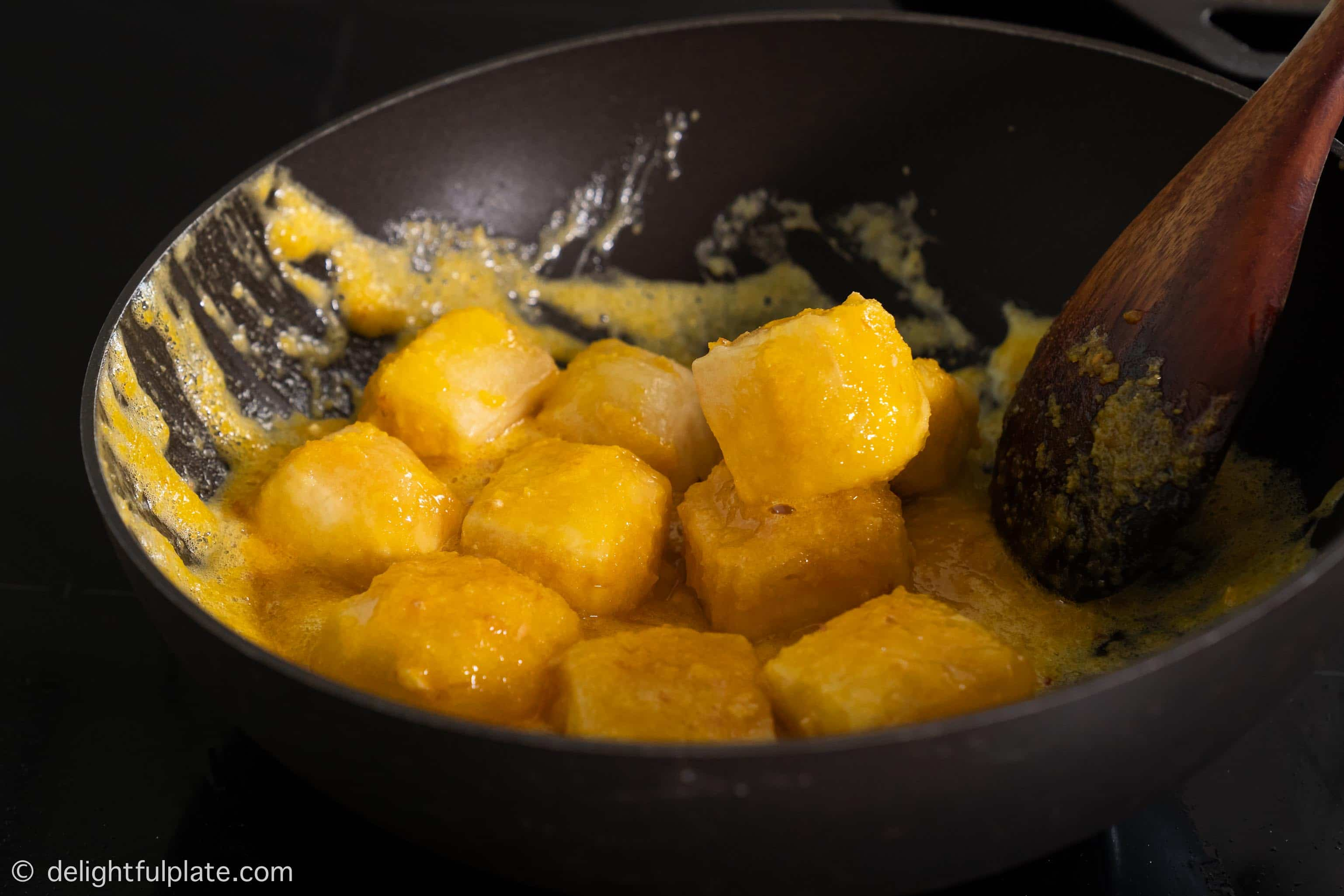 coating tofu with the salted egg sauce in a pan