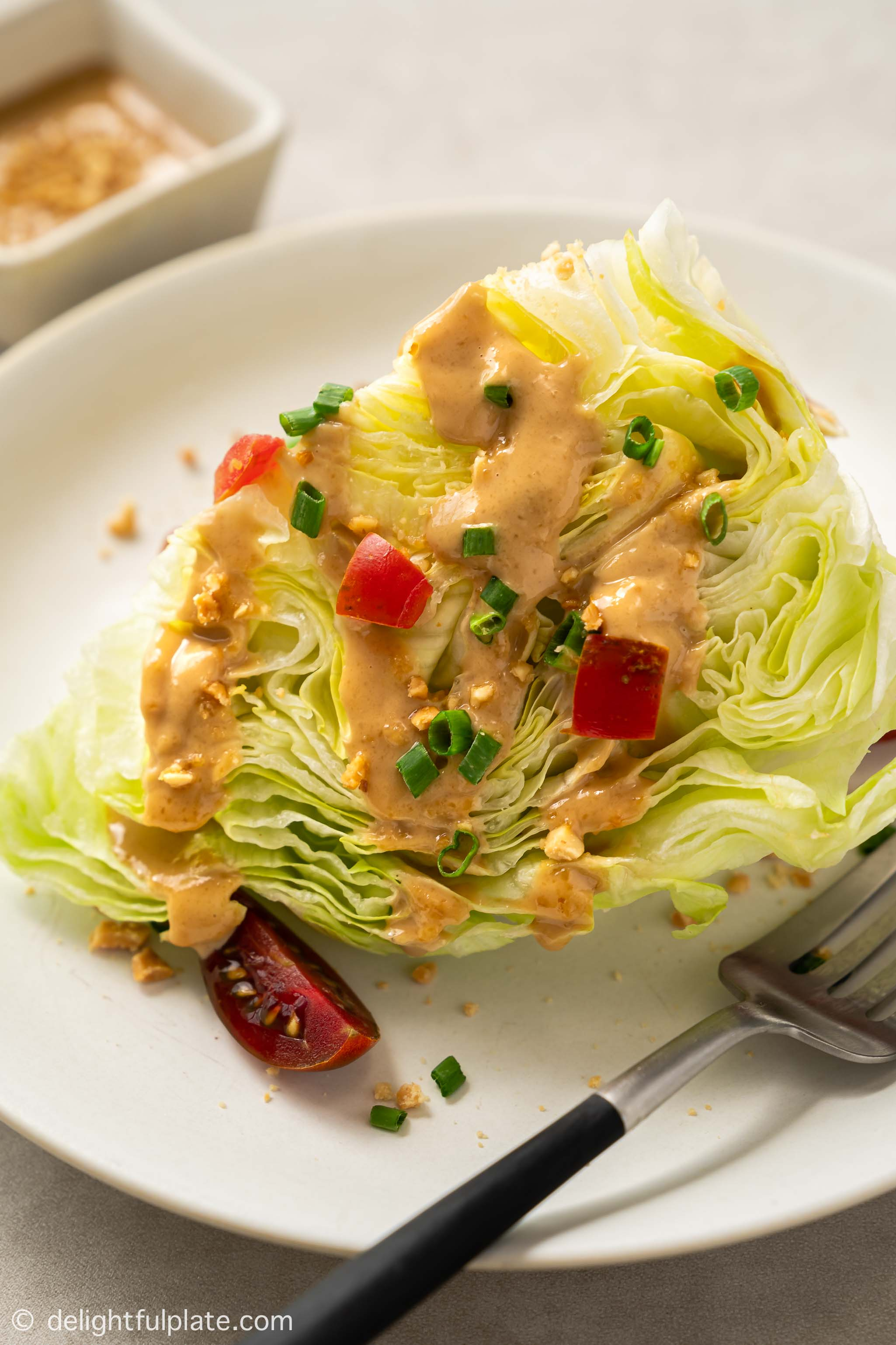 a wedge of iceberg lettuce served with peanut dressing