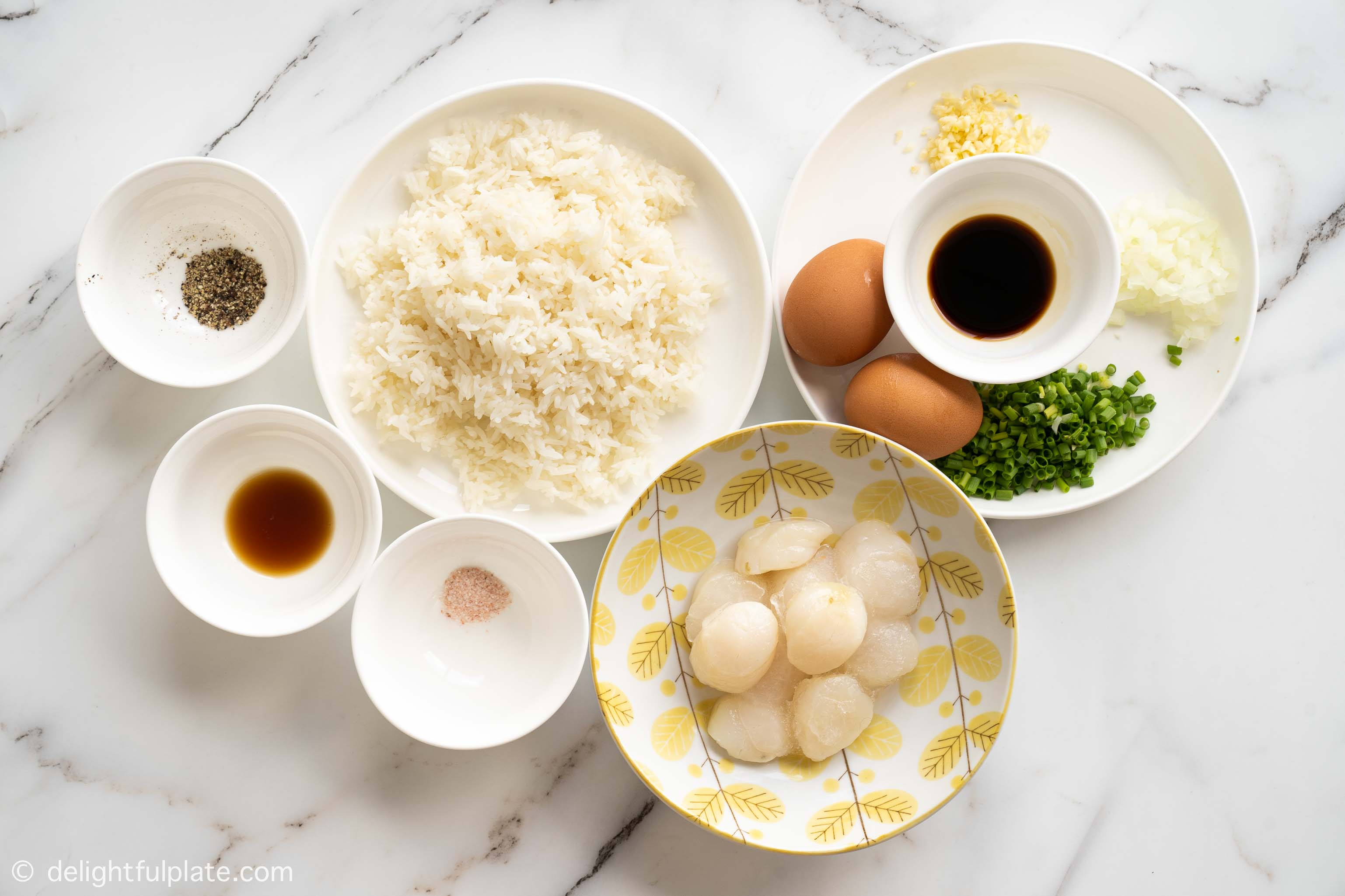 plates and bowls containing ingredients for scallop fried rice