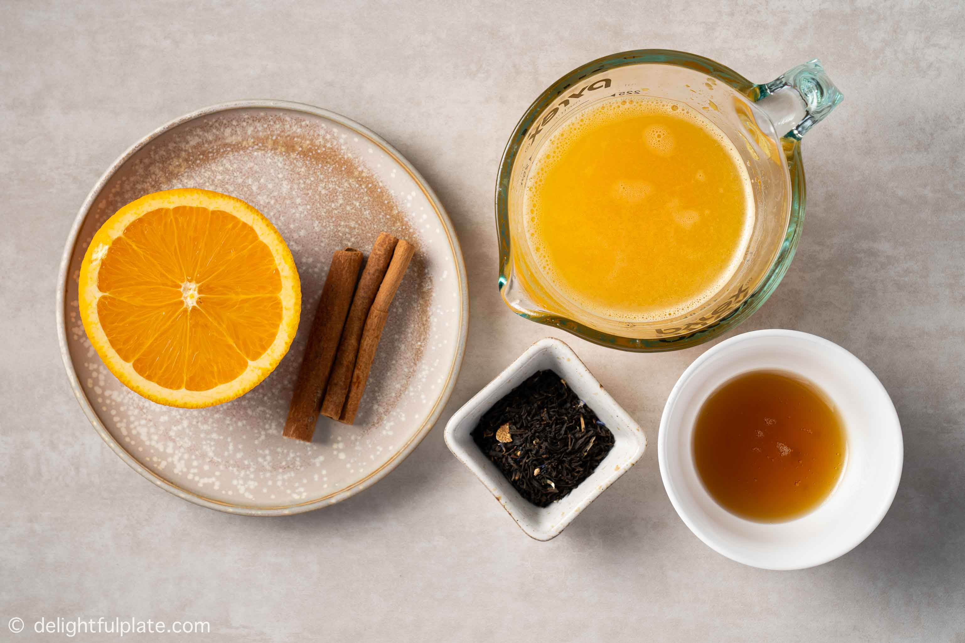 plates containing ingredients for orange cinnamon tea