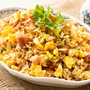 a plate of fried rice with bacon, eggs, carrots and onions